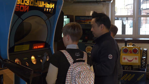Asian man and young caucasian woman stand in front of arcade game slot machine Footage