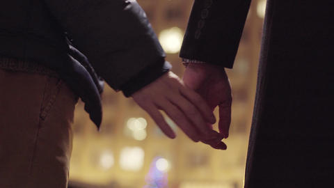 Couple of gay men are holding hands standing outside in cold winter street Footage