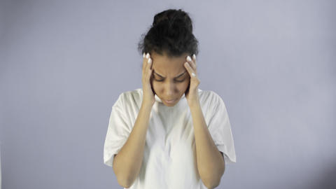 Beautiful young woman having terrible headache on grey background Live Action