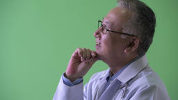 Closeup profile view of happy mature Japanese man doctor thinking Footage