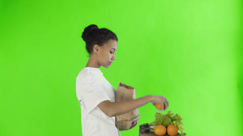 Happy woman load paper bag with organic healthy vegetables and fruits on chroma Footage