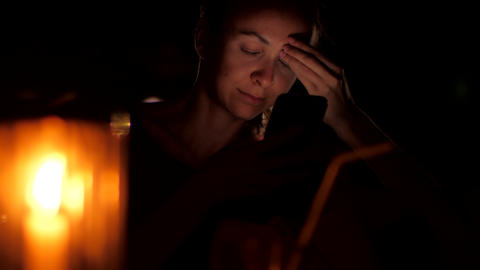 lady sits at night behind candle holding black smartphone Footage