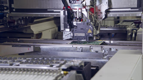Automated SMT machine placing electronic components on a board Live Action