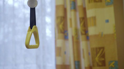 Closeup of hanging handle mounted to medical bed in ward with curtains Footage
