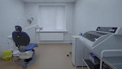 Empty dentistry room equipped with blue dental unit, furniture, operating lamp Live Action
