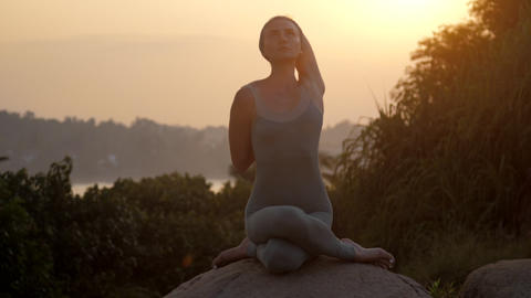 lady does cow faced asana sitting on huge stone slow motion Footage