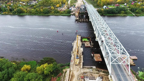 Active new bridge construction at area with two cranes nearby road and river Footage