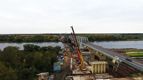Scenery of bridge construction zone with two cranes nearby roadway and river Live Action