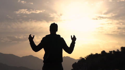 A guy throws his hands to the sides in awe of the nature at sunset, slow motion Live Action