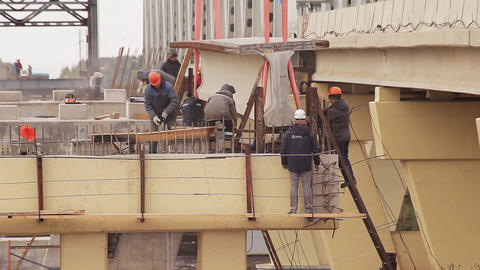 Scenery of male workers involved in action under huge lifted concrete beem Footage