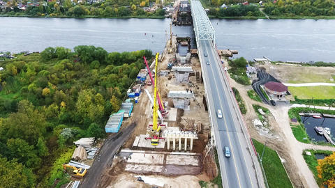 Sky view of active bridge construction at area nearby roadway and river Footage