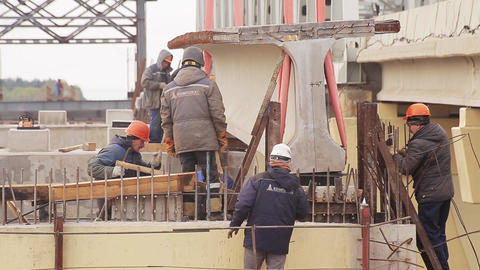 Camera shows male workers involved in action around huge lifted concrete beem Live Action
