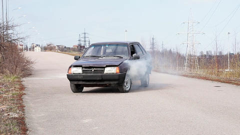 Old violet car is left on deserted dust road with smoking hood on cold day Footage