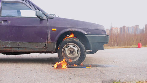 Old violet car is left on empty grey dust road with burning wheel on cold day Footage