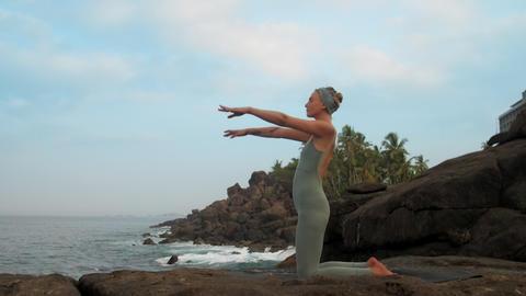 girl raises hands getting into ushtrasana at sea slow motion Footage