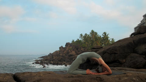 girl does kapotasana pose at tranquil ocean slow motion Footage