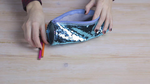 Hands get pencils out of a bluebug pencil case Footage