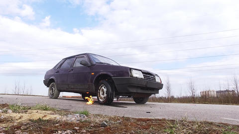 Old rusty violet car is left on deserted road with burning wheel on cold day Footage
