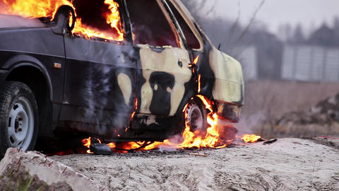 Big orange flames of fire completely burns dirty old car left on grey road Footage