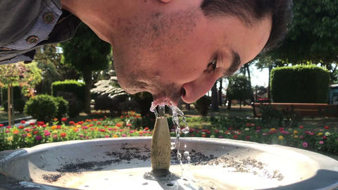 thirsty man drinking water from drinking fountain outdoors in park, summer heat Footage