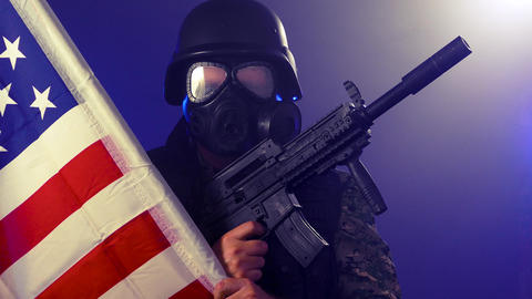 Soldier wearing gas mask holds rifle and US flag in fog Live影片