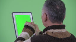 Closeup rear view of happy mature Japanese man using digital tablet Footage