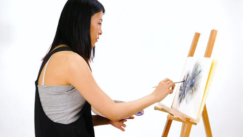 Artist ppainting at easel with palette focusing Footage