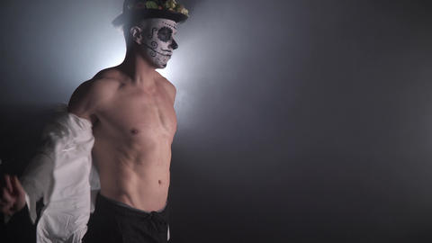 4k footage of a buff man with the mexican face paint taking off his shirt, 4k Live Action