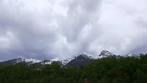 Quick clouds fly towards over mountain peaks, dusk view, overcast, time lapse Footage