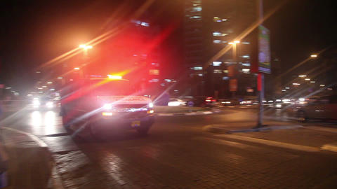 An ambulance drives down the street with the emergency lights on. With the sound Footage