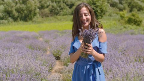 Cute female enjoying fragrant of lavender flowers Live Action