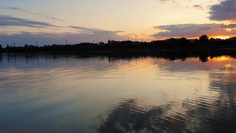 Wonderful sunset over the city horizon with reflection on the calm lake water in a silent summer Live Action