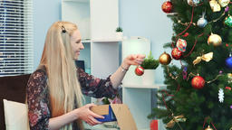Close up of Joyful woman hangs toys on Christmas tree taking them from the box Footage