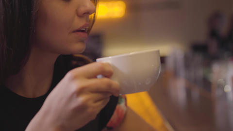 Close-up of attractive young woman enjoying her coffee sitting at the bar Footage