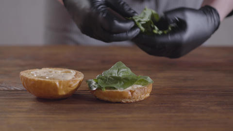 Hands of the chef in black kitchen gloves making burger close-up. The cook Footage