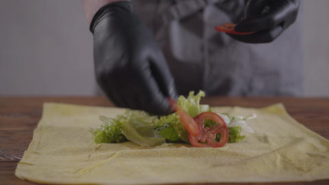 Hands of the chef in black kitchen gloves making shawarma close-up. The cook Footage