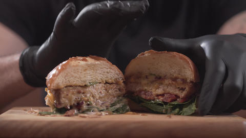Close-up male hands in black gloves taking half of tasty burger from the wooden Footage