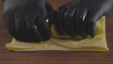 Close-up hands of the skill chef in black rubber gloves making shawarma. The Live Action