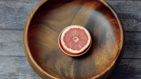 Fresh red grapefruit in wooden bowl, cut for squeezing fresh juice, citrus fruit in healthy menu. Footage