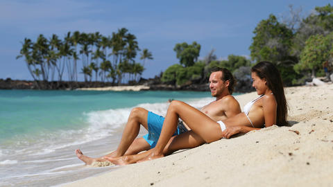 Couple relaxing on suntan beach vacation holiday - Happy young adults sunbathing Live Action