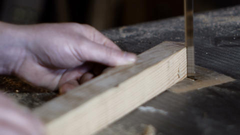 carpenter detail cuts a piece of wood with a band saw Footage