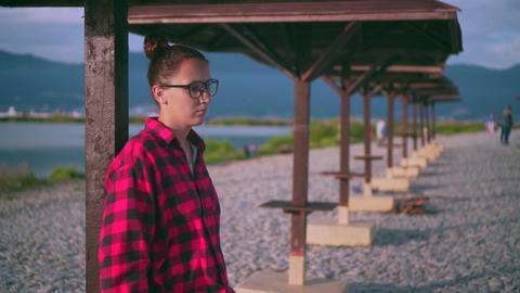 Beautiful young girl with glasses and a red checkered shirt relaxes. Background Footage
