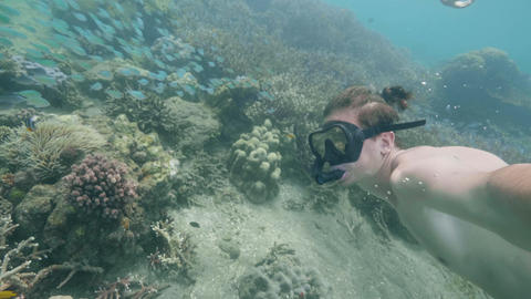 Man is snorkeling in ocean among coral reefs shooting himself on action camera Live Action