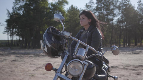 Pretty caucasian girl sitting on the motorcycle looking away. Hobby, traveling Live Action