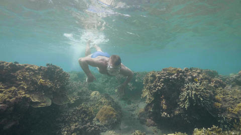 Man is snorkeling in ocean floor over the coral reefs on tropical vacation Footage