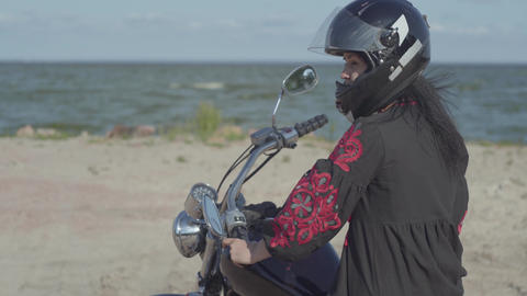Caucasian girl wearing black dress and helmet sitting on the motorcycle looking Live Action