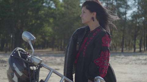 The girl with black hair standing at the motorcycle looking away in front of Live Action