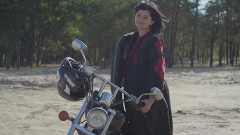 Pretty young caucasian brunette girl standing at the motorcycle looking away in Footage