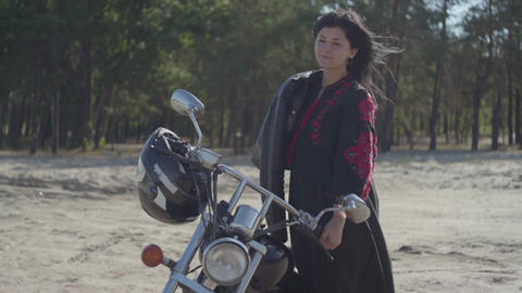 The girl with black hair standing at the motorcycle looking into the camera in Footage