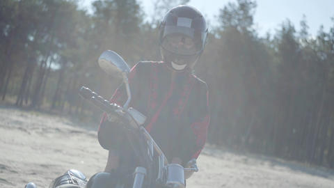 Front view of the girl in the helmet standing at the motorcycle in front of pine Footage